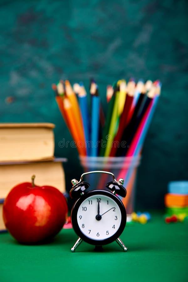 回到学校用品 书和红色苹果在绿色背景 免版税库存照片