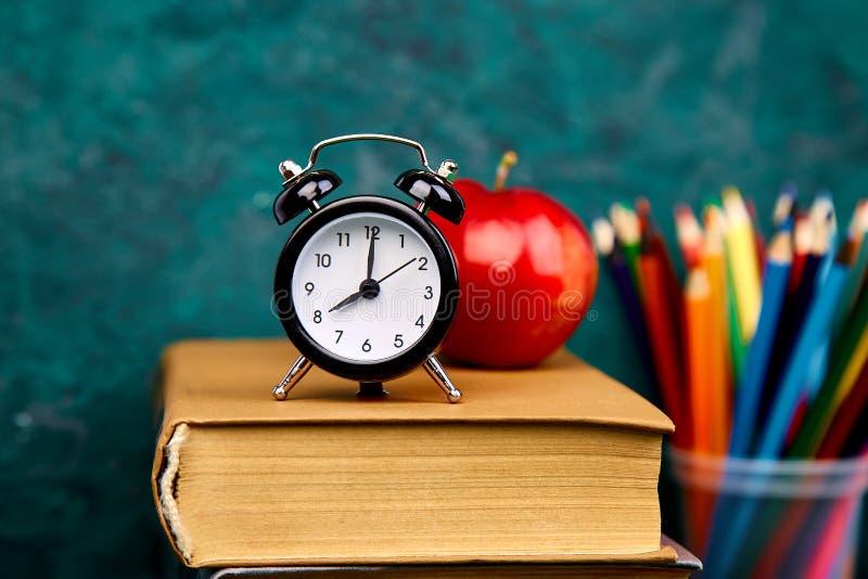 回到学校用品 书和红色苹果在绿色背景 免版税图库摄影