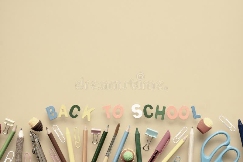 回到学校背景概念 回到学校木文本安排在与学校用品的黄色背景,文具存取机构 图库摄影