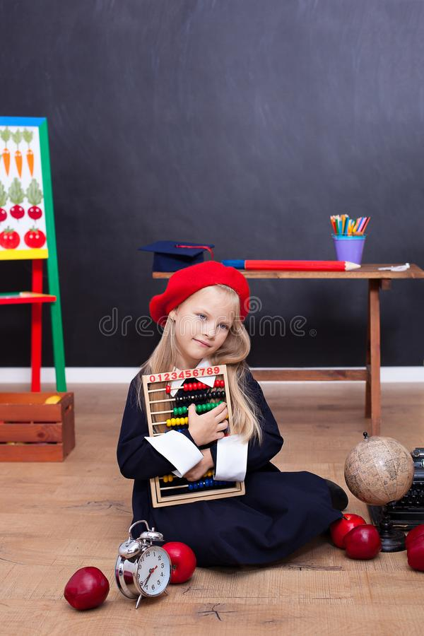 回到学校!坐在教室的校服的女孩 学生回答教训 女小学生在clas的教室 库存照片