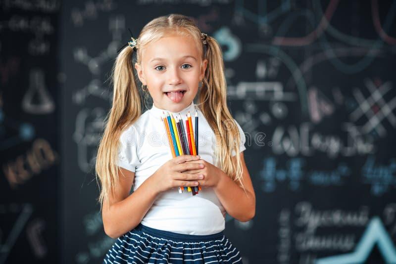 回到学校!女孩在她的手上站立与铅笔反对有学校惯例的黑板在学校 孩子是 免版税库存图片