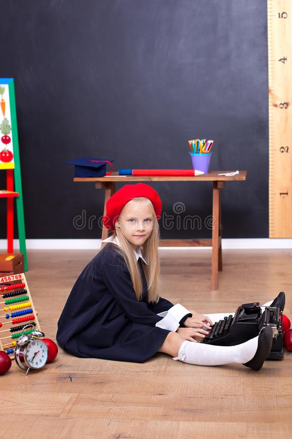 回到学校!女孩坐地板在学校并且拿着一台减速火箭的打字机 r 一点作家的新闻工作者 库存图片