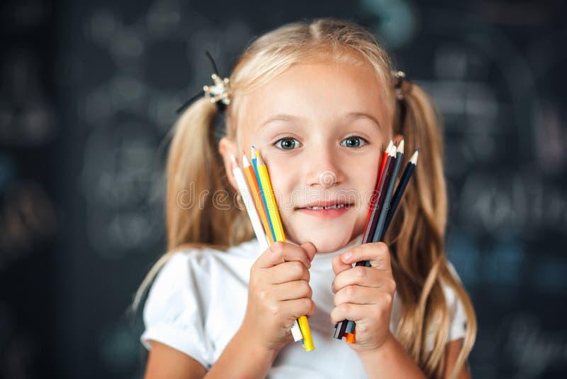 回到学校!女孩站立与拿着色的铅笔的女孩在面孔附近反对有学校的黑板的画象 免版税库存图片