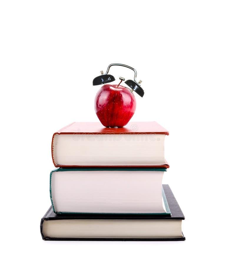 回到学校:在堆的苹果计算机闹钟书 库存照片
