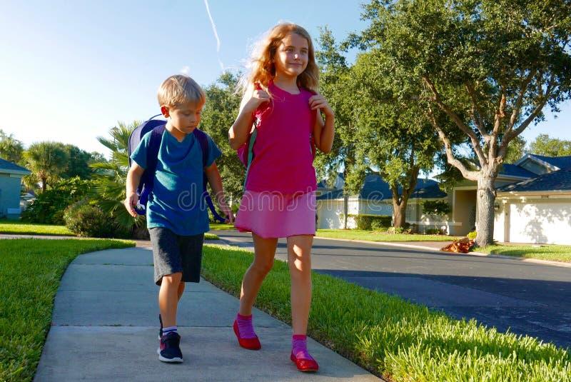 回到学校:走与背包的男孩和女孩 免版税图库摄影