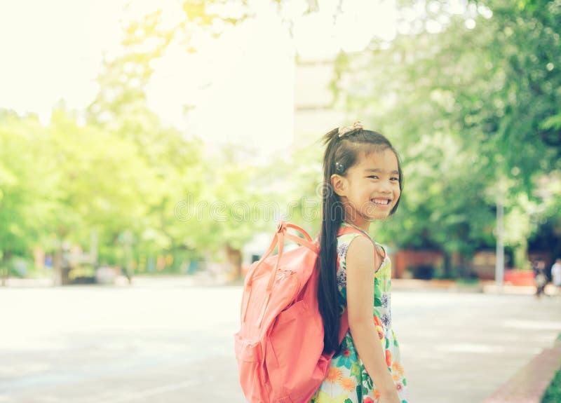 回到学校 从小学的愉快的微笑的女孩 免版税图库摄影