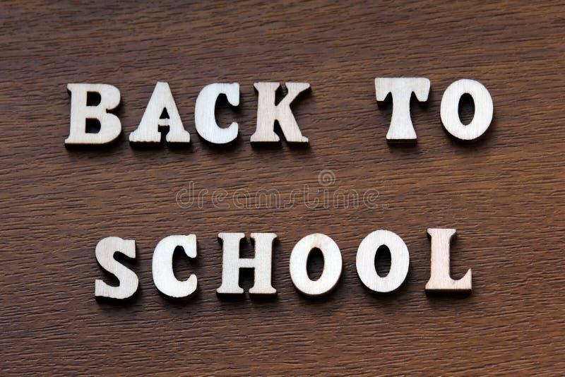 回到学校 在棕色背景的木信件 免版税库存照片