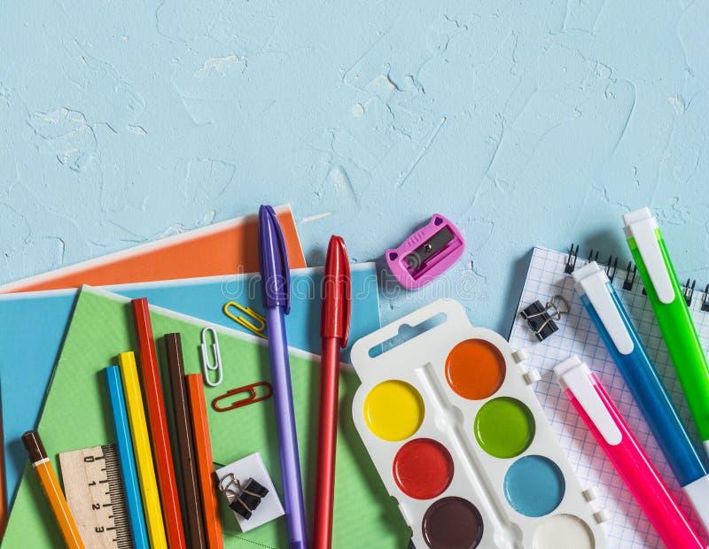 回到学校 学校辅助部件-笔记本,笔,铅笔,在蓝色背景的油漆,顶视图 登记概念教育查出的老 平的位置 库存图片