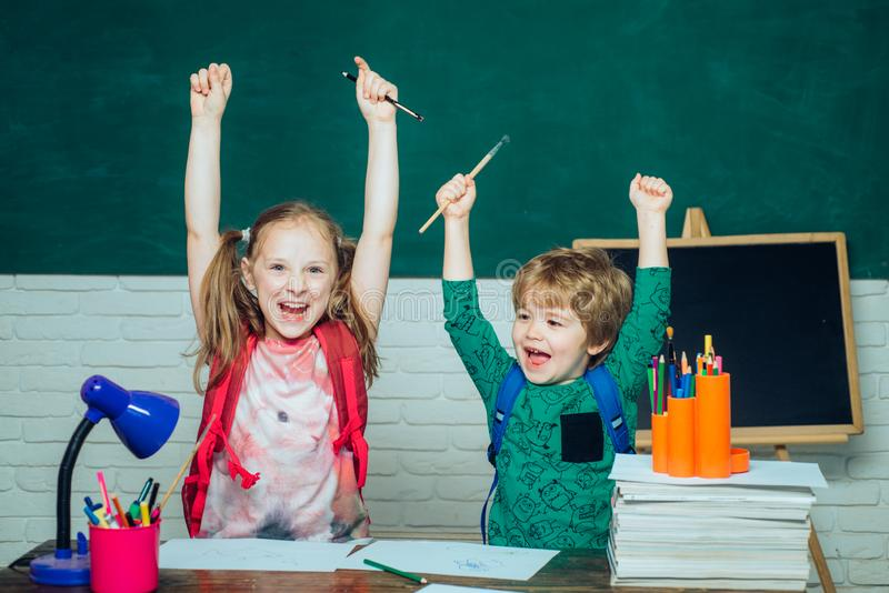 回到学校-教育概念 快乐的微笑的小男孩和逗人喜爱的女孩获得乐趣反对黑板 免版税库存图片