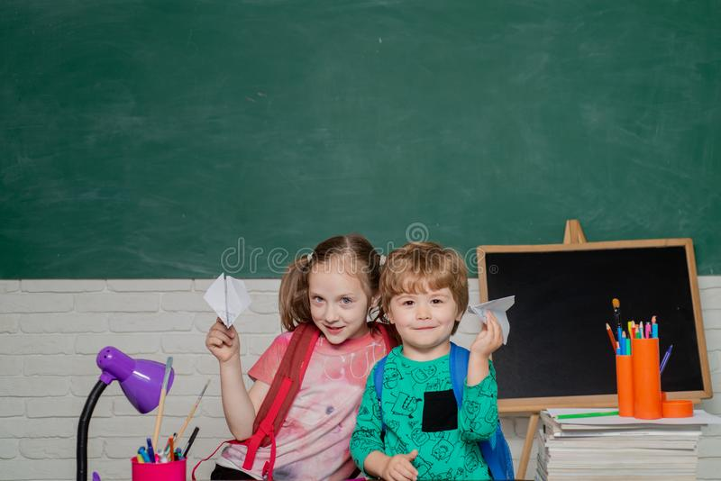回到学校-教育概念 第一次教育 愉快的逗人喜爱的辛勤孩子坐在书桌户内 免版税库存照片