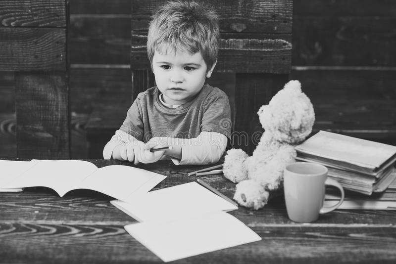 回到学校 看在木桌上的孩子习字簿 拿着五颜六色的铅笔的小被集中的男孩 图库摄影