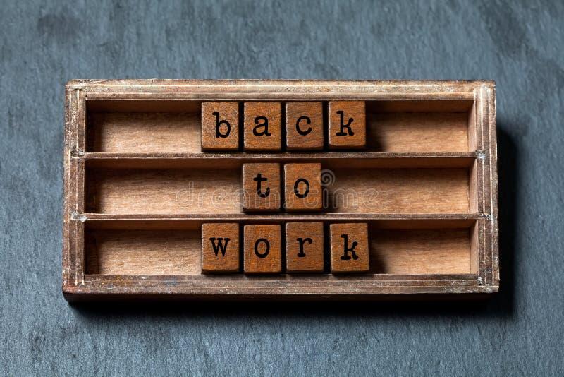 回到工作 正面诱导行情 葡萄酒箱子,与老牌信件的木立方体词组 被构造的灰色石头 免版税库存照片