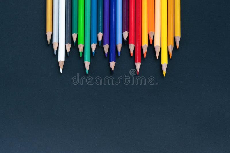 回到概念学校 关闭颜色铅笔堆在黑背景的铅笔鸟嘴射击与拷贝空间 免版税图库摄影