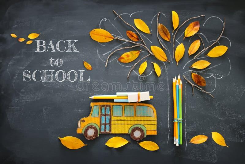 回到概念学校 校车的顶视图在树剪影旁边的图象和铅笔与秋天烘干在教室blackbo的叶子 免版税图库摄影