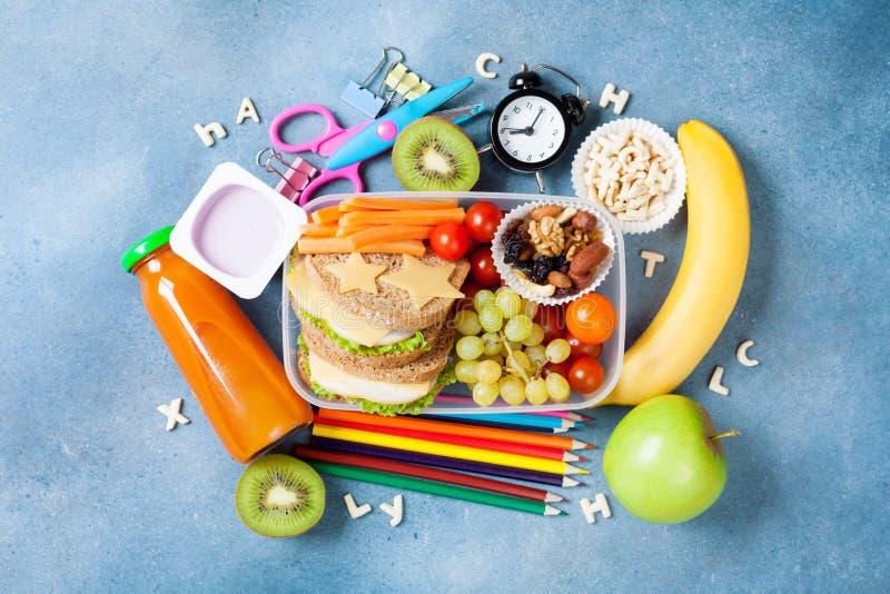 回到概念学校 营养午餐盒和五颜六色的文具在蓝色台式视图 库存图片