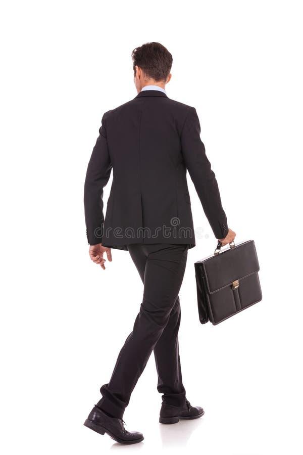回到观点的有公文包的一个走的商人 免版税库存照片