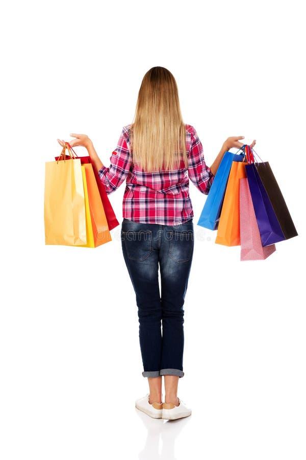 回到观点的有购物袋的去的妇女 库存照片