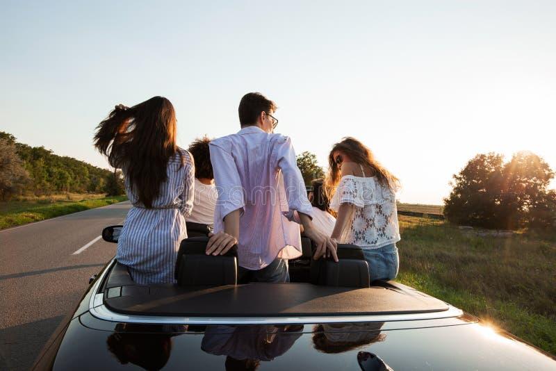 回到视图 年轻人在黑敞蓬车在乡下公路坐一好日子 免版税库存照片
