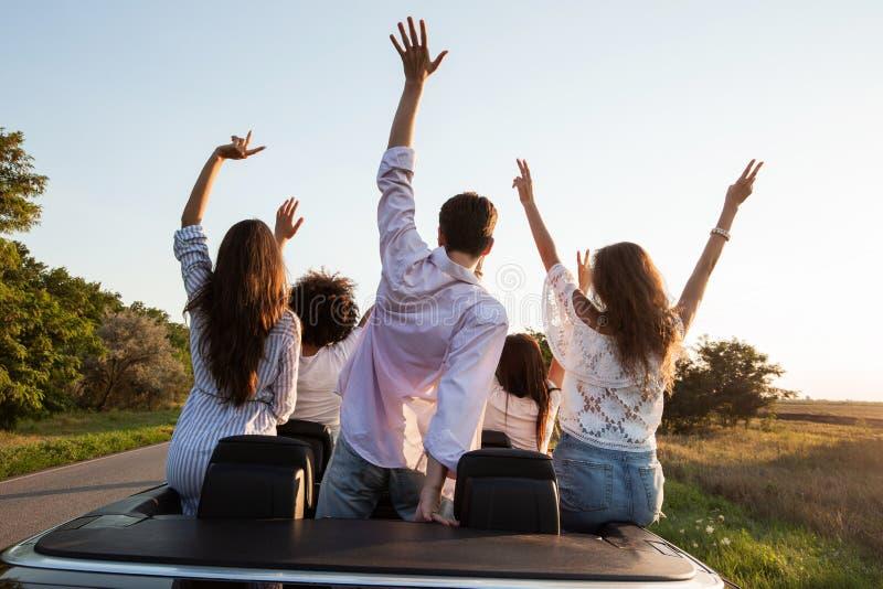 回到视图 年轻人是和握手在黑敞蓬车坐乡下公路在一好日子 库存图片