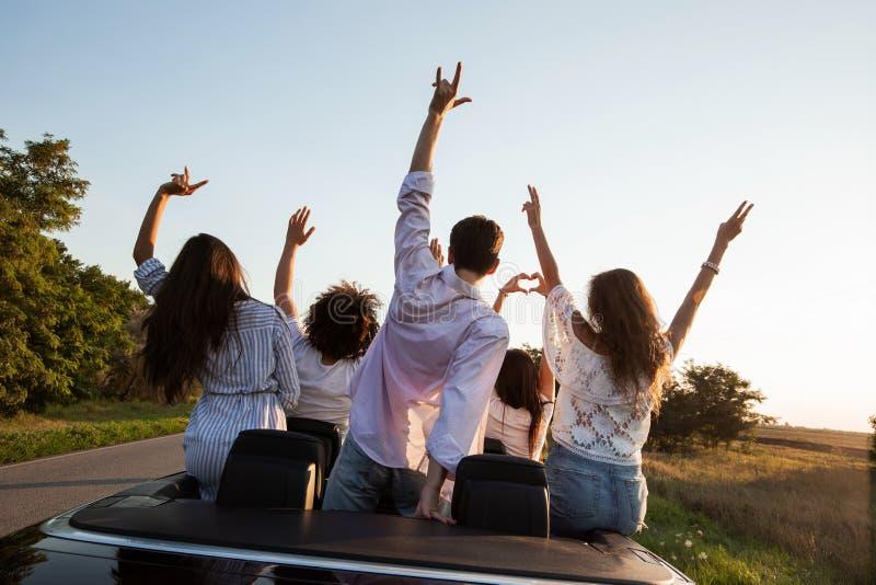 回到视图 年轻人是和握手在黑敞蓬车坐乡下公路在一好日子 库存照片