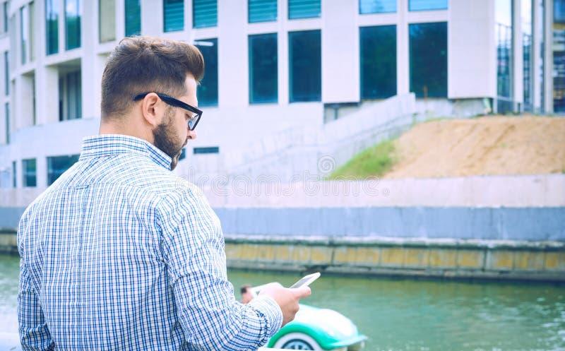 回到视图 行家人在河的堤防站立并且使用智能手机 牛仔布衬衣的人站立 免版税图库摄影