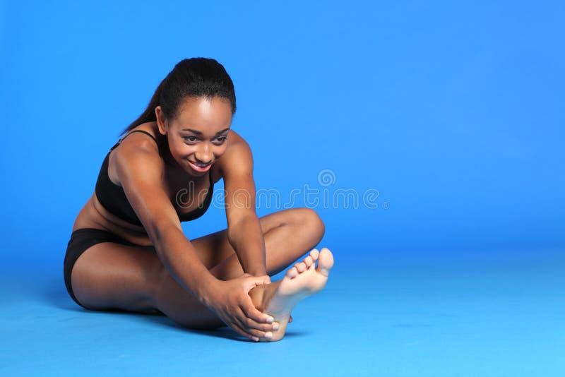 回到黑人执行腿筋舒展妇女 图库摄影