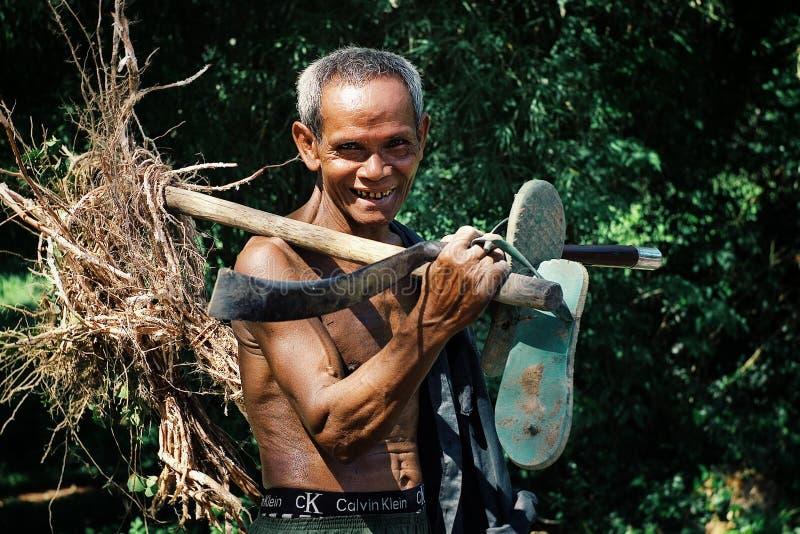 回家从他的有有些根的农场和他的工具的年长资深高棉人在他的手上 库存照片