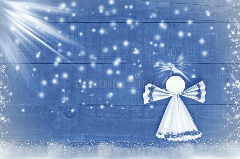 回家做的圣诞节纸天使在蓝色,多雪的木背景 工艺 库存图片
