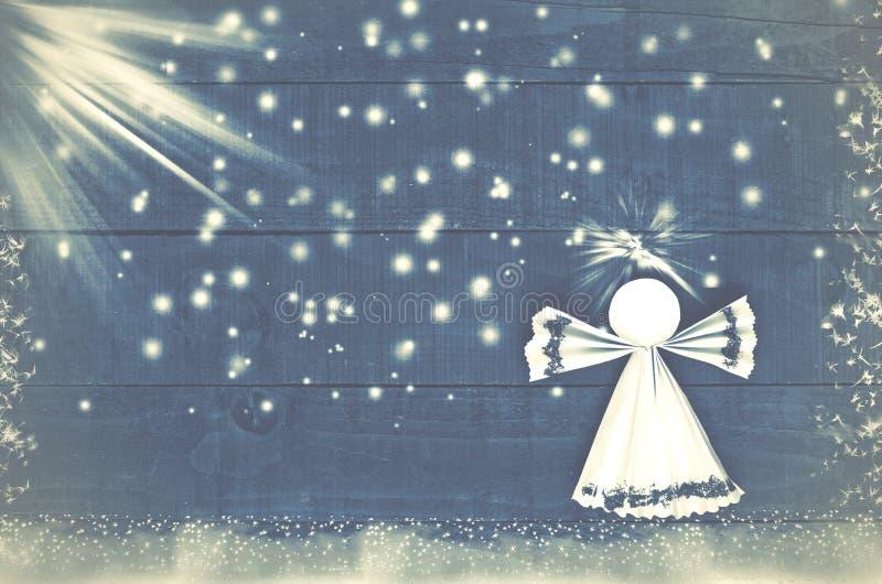 回家做的圣诞节纸天使在蓝色,多雪的木背景 免版税库存照片