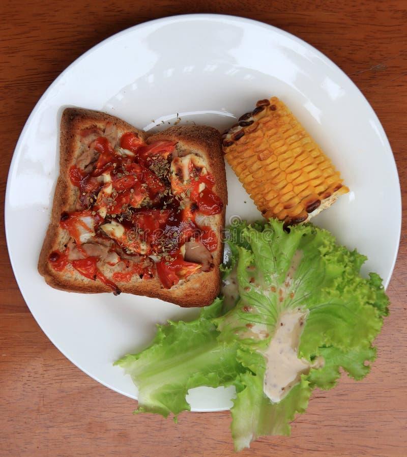回家做的薄饼在正方形切的面包用烤玉米和莴苣在白色圆的板材在木桌上 免版税图库摄影