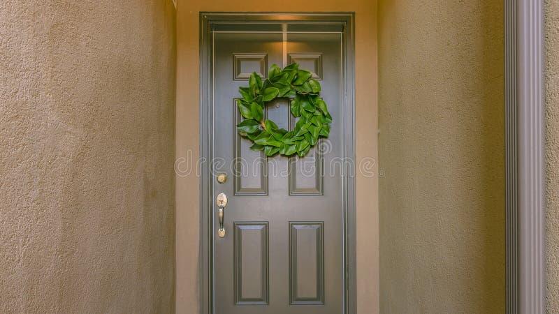 回家的入口与花圈在灰色大门 免版税库存图片