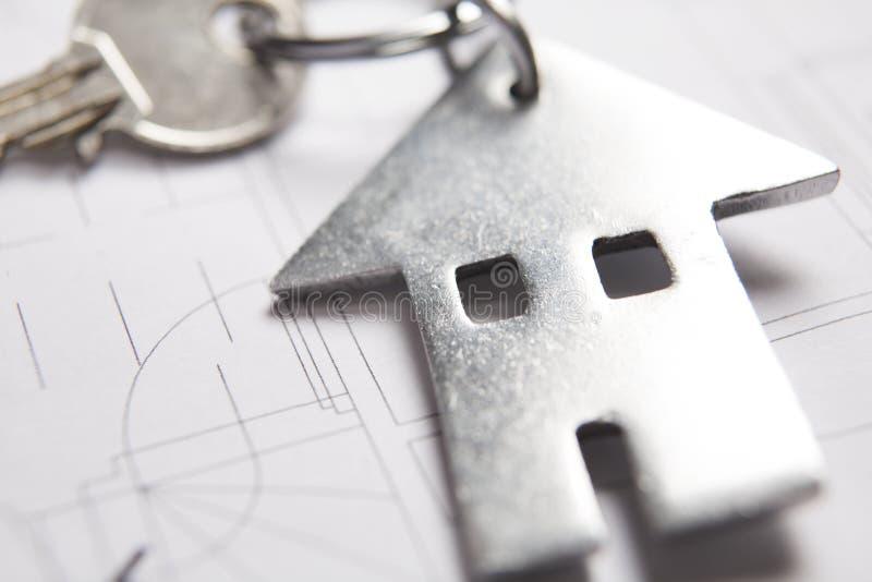 回家的钥匙在与议院形状的钥匙圈的建筑师计划 免版税库存照片