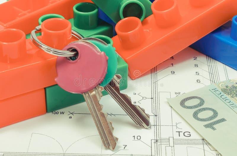 回归键、五颜六色的玩具积木和金钱在安置的计划 修造的房子概念 库存照片