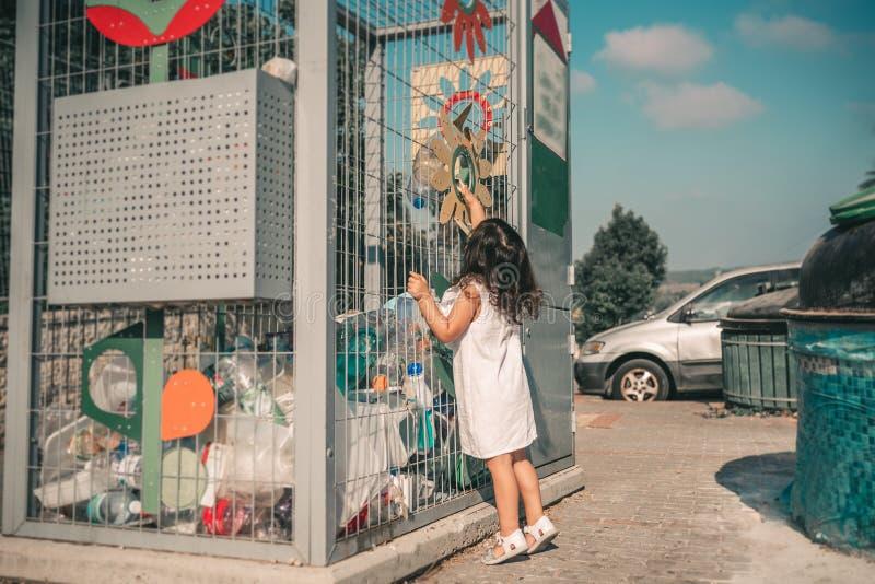 回收塑料水瓶的女孩 条板箱塑料水瓶准备好回收在容器 库存图片