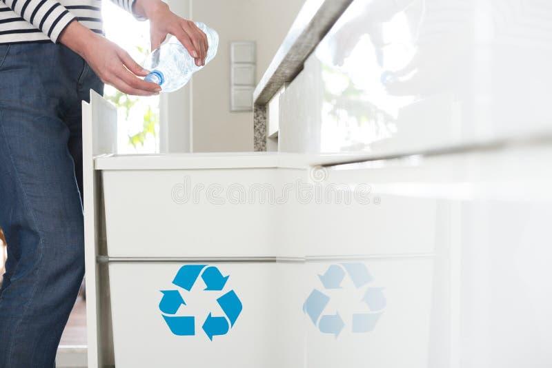 回收塑料瓶的明白的主妇 免版税库存图片