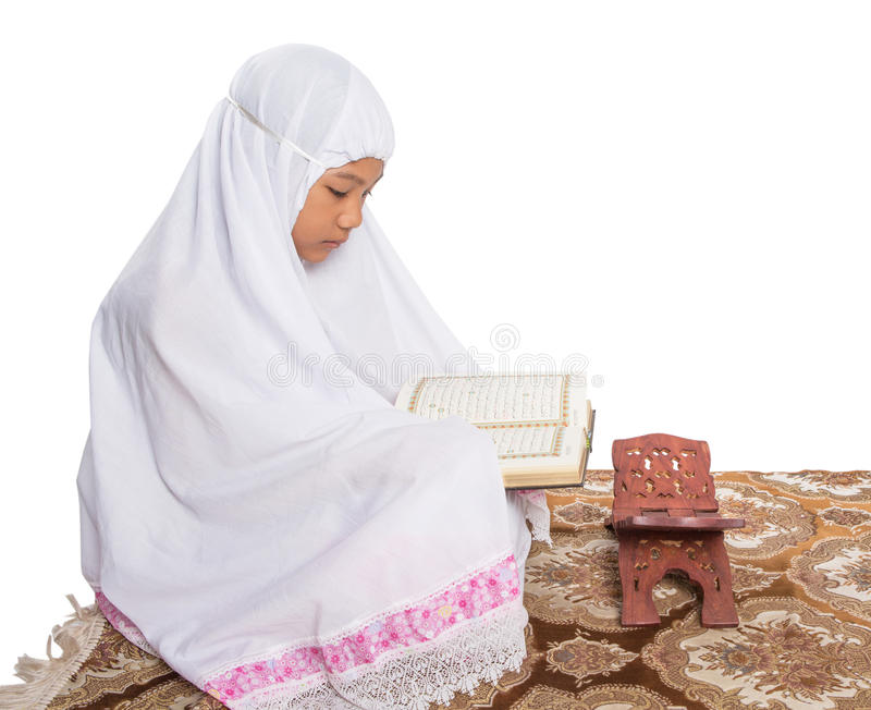 年轻回教女孩读书Al古兰经v 库存照片