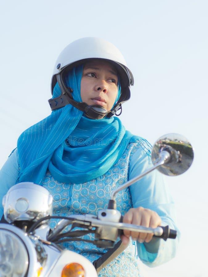 回教妇女乘驾马达自行车 库存照片