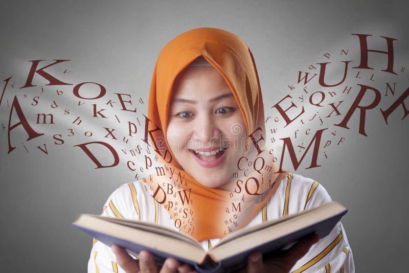 回教妇女和书 免版税库存图片