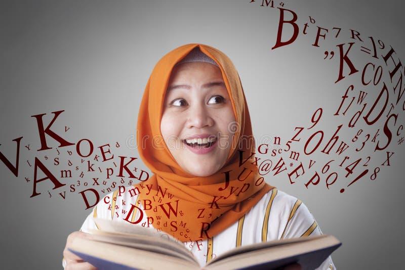 回教妇女和书 免版税图库摄影
