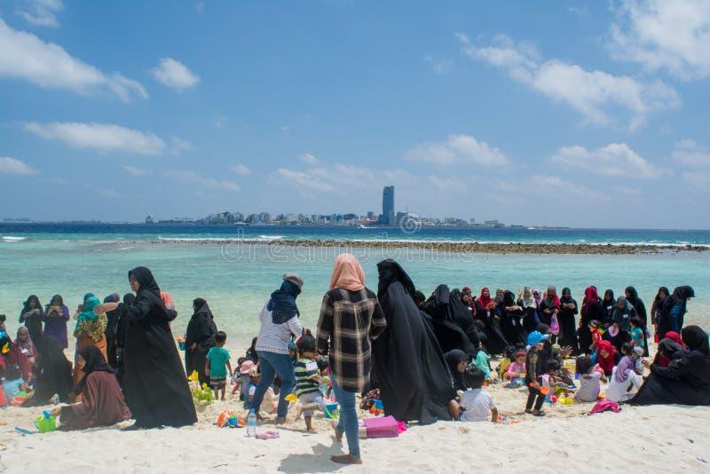 回教妇女和孩子有党在海滩 免版税库存图片
