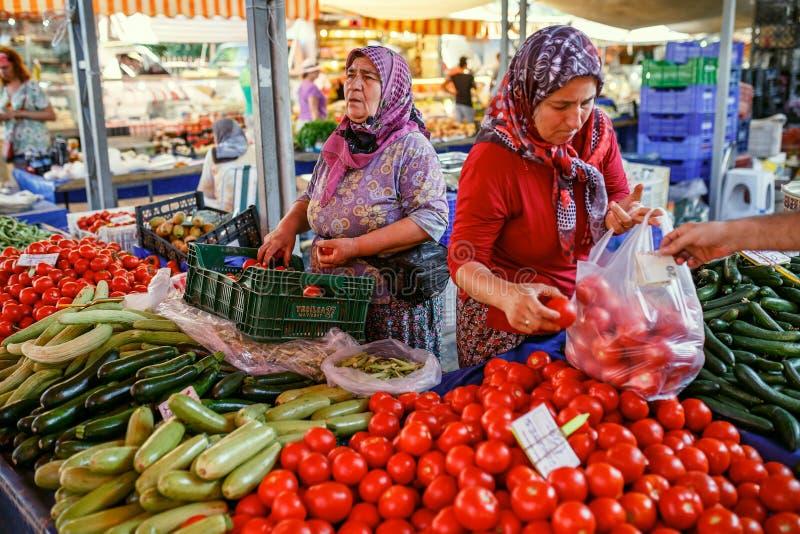 回教妇女在市场上的卖菜 Kemer,土耳其 免版税库存图片