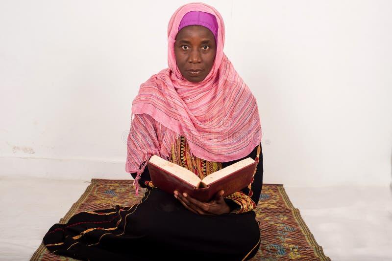 回教妇女坐的祈祷读古兰经 库存图片
