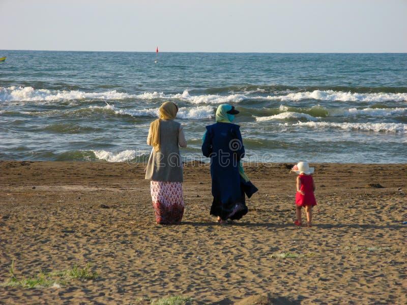 回教妇女hijab走的海滩 hijab的回教妇女走在海滩的里海在伊朗,Anzali 库存图片
