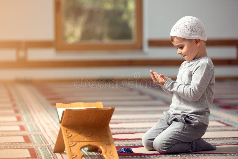 回教孩子在清真寺祈祷,小男孩祈祷对上帝、和平和爱在圣洁月赖买丹月 库存照片