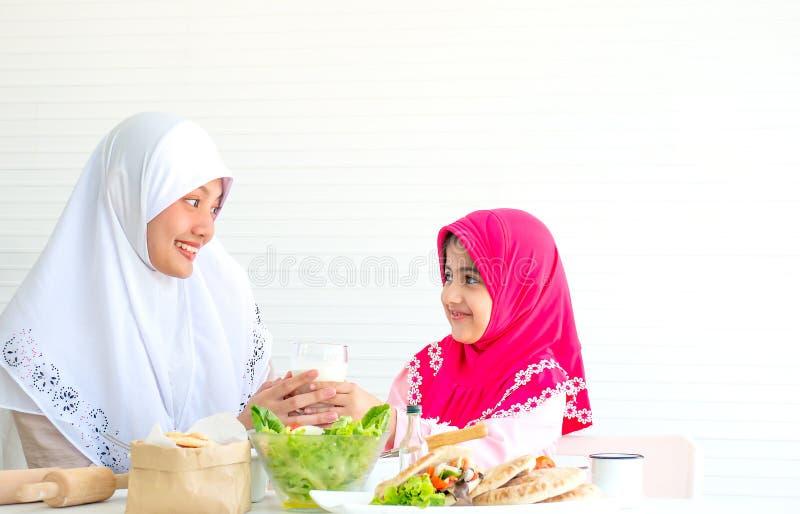 回教母亲和女孩互相神色和微笑也拿着与碗的牛奶在桌上的菜沙拉在前面 库存照片