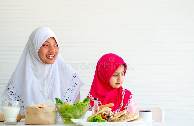 回教母亲和她的女儿在同一个方向看用在桌和白色背景上的菜沙拉 免版税图库摄影