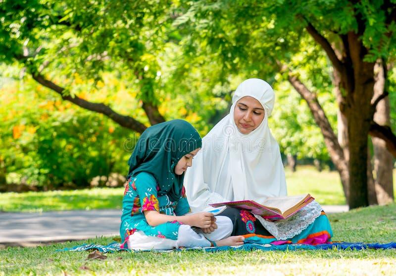 回教母亲教她的女儿读了解的好的生活方式宗教课本  他们在绿色庭院里停留 免版税库存图片