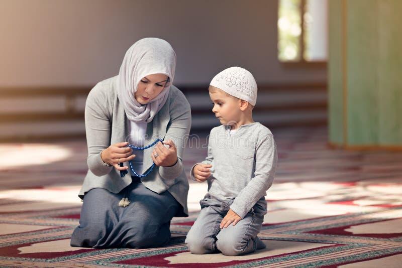 回教母亲教她的祈祷在清真寺里面的儿子 免版税库存照片