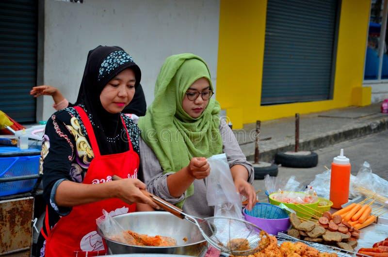 回教泰国妇女烹调在街道货摊在食物街道义卖市场北大年泰国 图库摄影