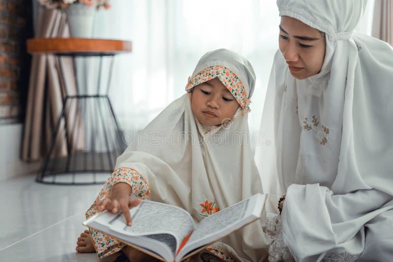 回教父母和女儿读书古兰经 图库摄影